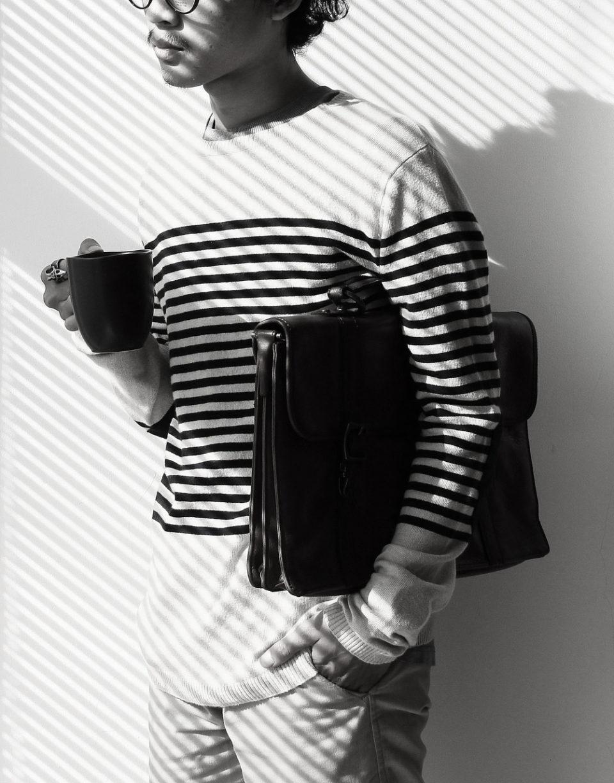 кучерявый парень пьет кофе и держит портфель под мышкой